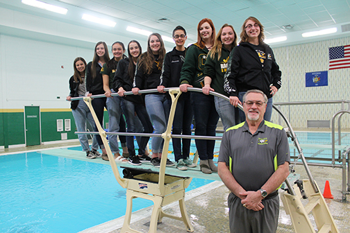 Girls standing on diving board with coach